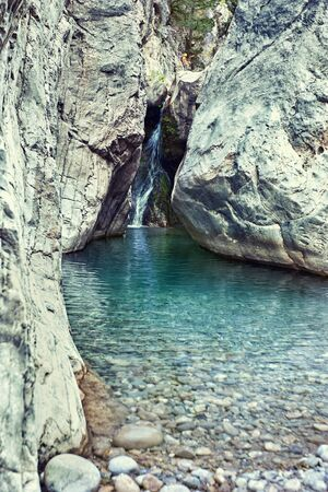 Cascade on the mountain river in the canyon in summer. Stock Photo