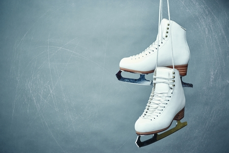 A pair of female white skates on a gray background. Archivio Fotografico