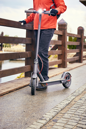 Athletic man with a backpack on the street with kick scooter.