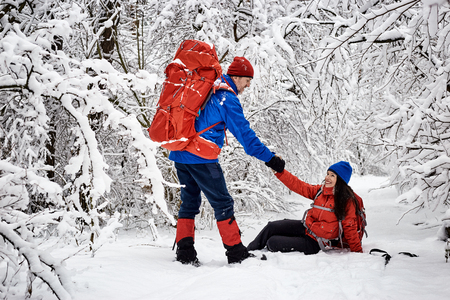 Walk the couple in love on a hike through the winter forest. Stock Photo