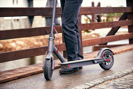 Use of scooter as a means of transportation on the street. Foto de archivo