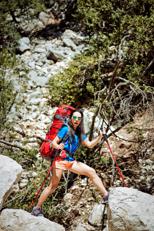 Summer hike in the canyon with a red backpack and tent. Stock Photo