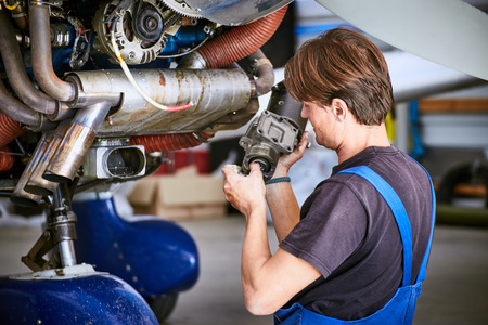 Removal and repair of an engine starter of an airplane by a service worker. Imagens