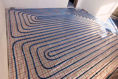 Laying pipes for floor heating at the construction site of the house. Фото со стока