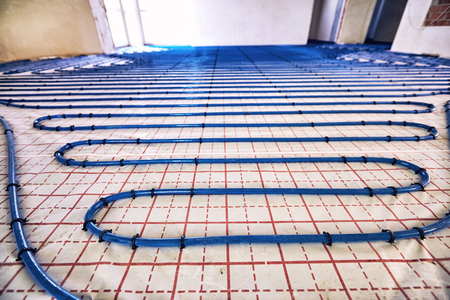 Laying blue pipes for floor heating at the construction site. Stock Photo