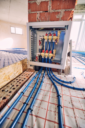 Laying blue pipes for floor heating at the construction site. Фото со стока