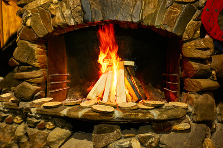 Burning of a tree in a brick fireplace. Fireplace with flaming fire. Imagens