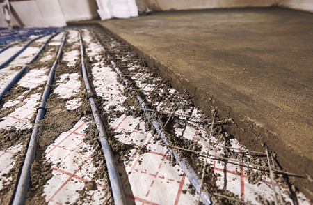 Laying pipes for floor heating at the construction site of the house. Stock Photo
