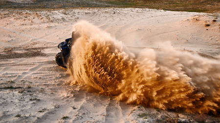 Racing powerful quad bike on the difficult sand in the summer. Stock Photo