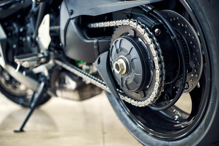 Detail of a motorcycle rear chain with exhaust pipes. Rear view of a motorcycle with the focus on chain.
