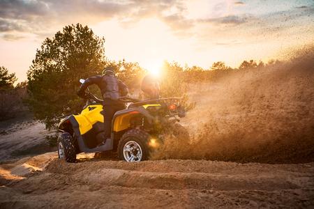 Course dans le sable sur un quad à quatre roues motrices. Banque d'images