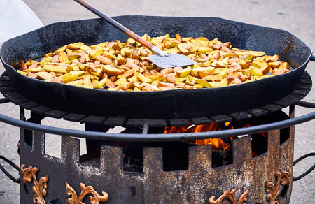Traditional cooking of fried potatoes in a pan in the countryside.