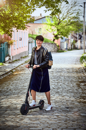 Using an electric scooter as a means of transportation on the street.