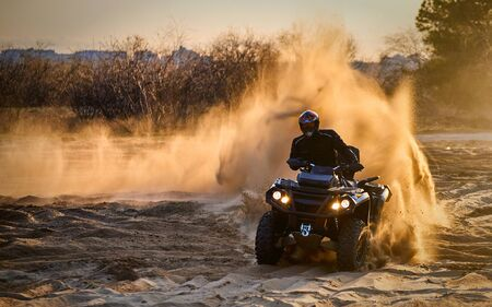 Racing in the sand on a four-wheel drive quad.