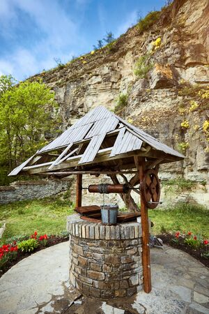 Real acting wooden well in the countryside in summer.