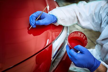 Professional painting of a red car on the service