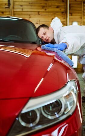 Professional polishing at the service of a red car. Stock Photo