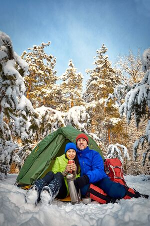 Camping in the winter forest of a couple in love.
