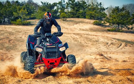 Racing powerful quad bike on the difficult sand in the summer.