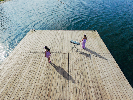 Aerial view from above of two girls singing at the old pier. Surrealism