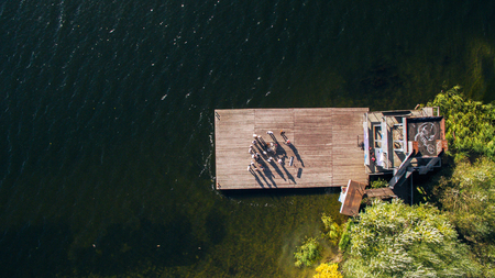 group of musicians and singers standing on the old pier on the river. Surrealism. View from above. Aerial view