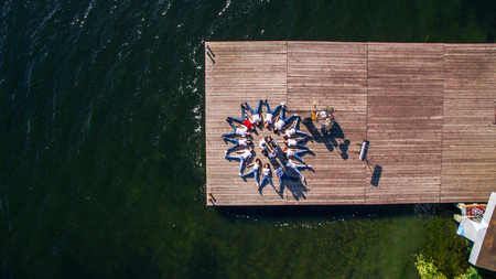 A group of musicians and singers lie on the pier on the river. Surrealism. View from above. Aerial view
