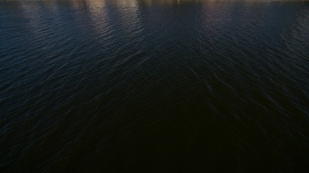 Top view of the black water of the lake at night.