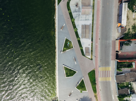 Aerial top view of the city embankment, road, lake, skate park. Two girls are lying on a green lawn. Surrealism.