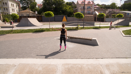 Young slim girl in sportswear is engaged in sports in the skate park