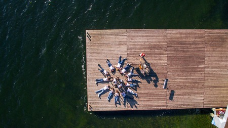 aerial view. Young people lie on a wooden bridge against the background of the river. musical instruments lie on the bridge. Surrealism.