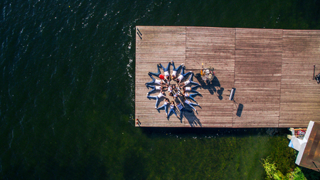 aerial view. Young people lie on a wooden pier against the background of the river. musical instruments lie on the bridge. Surrealism. Banco de Imagens