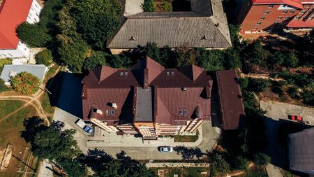 Aerial view of a new large modern comfortable home with a brown tiled roof. View from above
