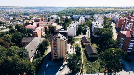 Aerial view of a small city with new large modern comfortable houses with a brown tiled roof on a summer day. View from above
