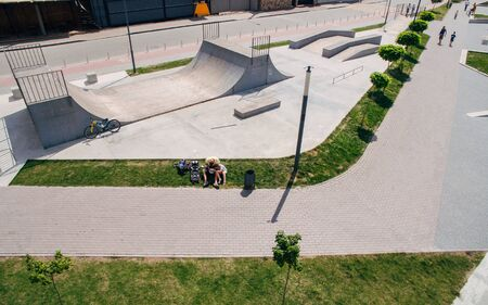 Aerial view of the skate park. A father and his little son are resting in a skate park. Healthy lifestyle concept Stock fotó
