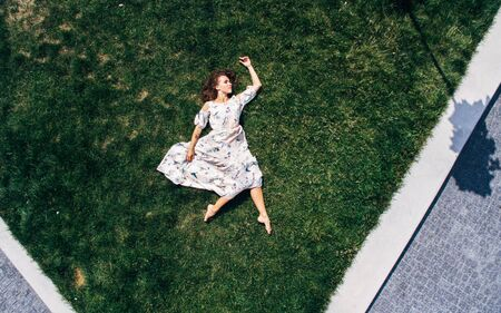 Surrealism. The girl lies on a green lawn in a dress. Aerial view Stock fotó