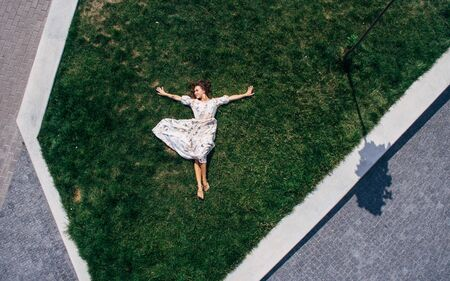 Surrealism. Happy red-haired girl lies barefoot on a green lawn in a dress. Aerial view