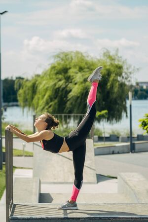 Girl doing exercises and twine on a sports field by the lake