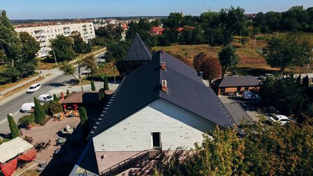 Aerial view of a small city with new modern comfortable houses with a black tiled roof on a summer day. View from above Stock fotó