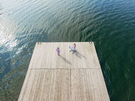 Aerial view . Two girls sing on the pier. Surrealism