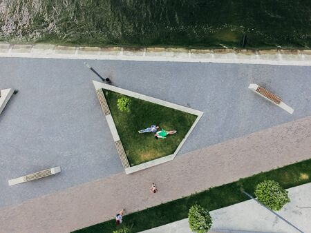 Two girls are lying on a green lawn near a lake on the waterfront. Aerial view. Surrealism Stock fotó