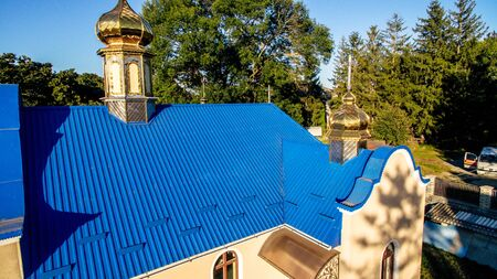 View of the new modern church with a blue tiled roof on a summer evening forest background.