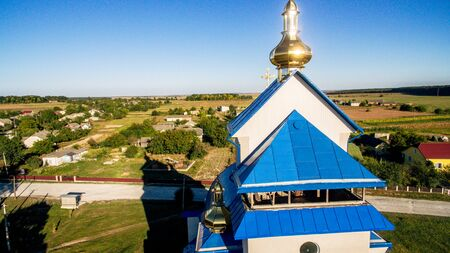 Aerial view of a new modern church with a blue tiled roof on a summer sunny day in a small village.