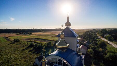 Aerial view of a new modern church with a blue tiled roof on a summer evening in a small village. Stock fotó