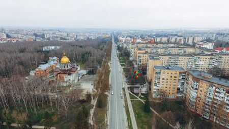 Aerial view of a street with multi-storey prefabricated houses, a church, a park and a highway in early spring.