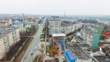 Aerial view of a street with multi-storey prefabricated houses, a church and a highway. Stock fotó