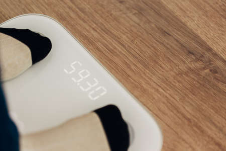 Girl Measures Weight on Smart Scales. Modern Electronic Device. Imagens