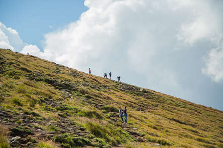 People descend down a large green mountain range. Mountain Hiking