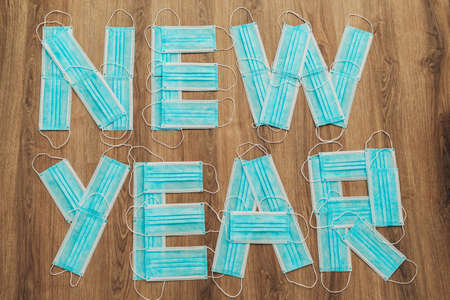 Capital Letters New Year Composed of Blue Medical Masks on a Brown Background