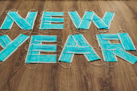 Letters New Year Composed of Blue Medical Masks on a Brown Background