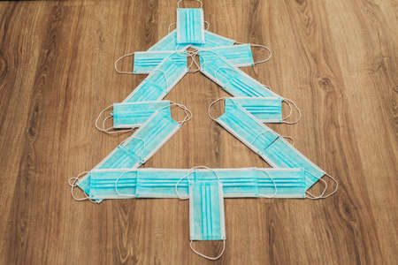 Christmas Tree Made of Blue Medical Masks on a Brown Background